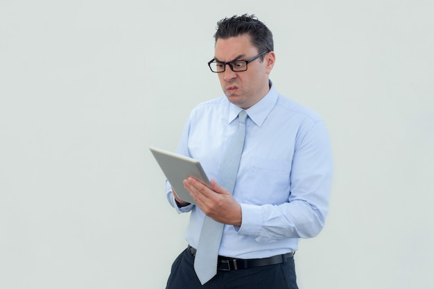 Annoyed shocked businessman in eyeglasses using tablet