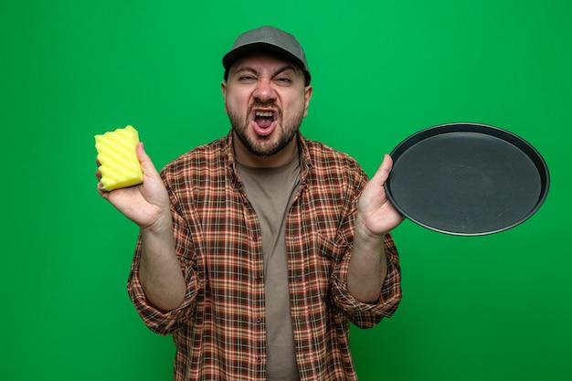 Uomo delle pulizie slavo infastidito che tiene piatti e spugna