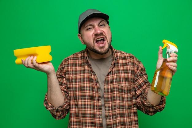 Uomo delle pulizie slavo infastidito che tiene in mano una spugna e un detergente spray