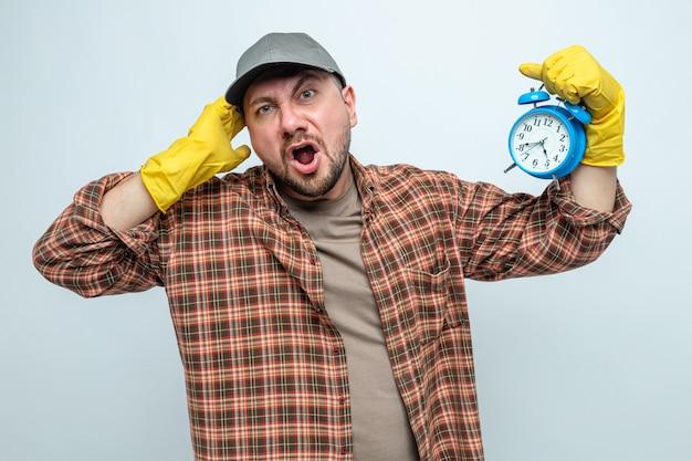 Uomo delle pulizie slavo infastidito con guanti di gomma che tiene la sveglia