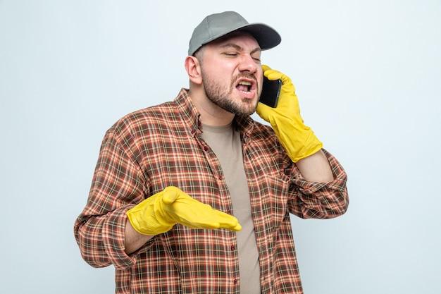 Раздраженный славянский уборщик в резиновых перчатках кричит на кого-то по телефону