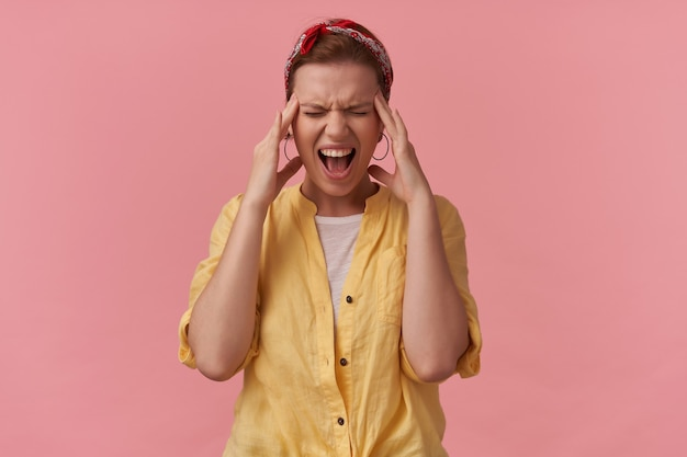 Раздраженная напряженная молодая женщина в желтой рубашке с повязкой на голове кричит, касаясь ее висков, и у нее болит голова над розовой стеной