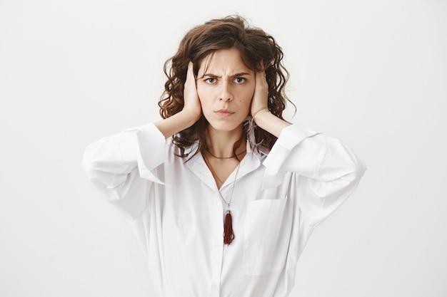 Раздраженная надутая женщина, закрывающая уши, обеспокоена