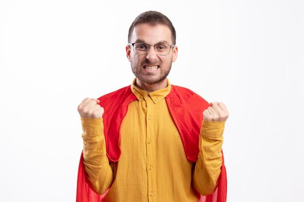 빨간 망토와 광학 안경에 짜증이 슈퍼 히어로 남자는 흰 벽에 고립 된 주먹을 유지