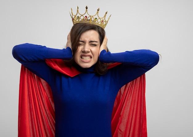 白い壁に隔離された手で王冠と赤いマントの耳を閉じるイライラしたスーパーウーマン