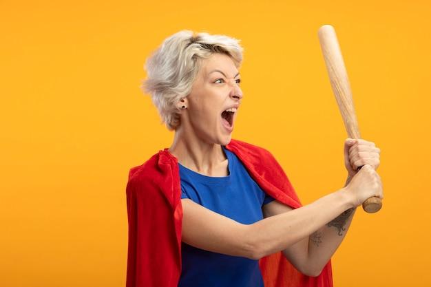 La superdonna infastidita con mantello rosso tiene la mazza da baseball e guarda il lato isolato sulla parete arancione