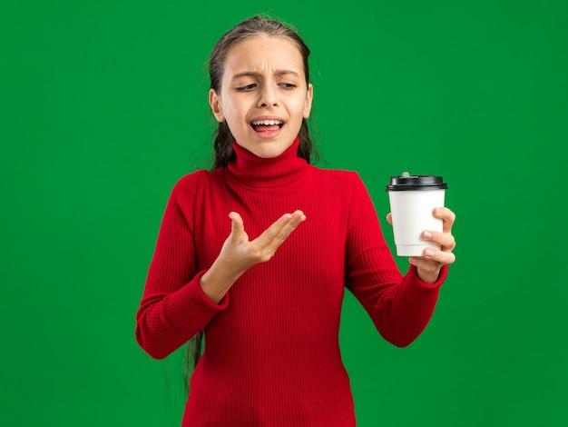 녹색 벽에 격리된 플라스틱 커피 컵을 보고 가리키는 성가신 10대 소녀
