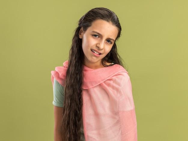 복사 공간이 있는 올리브 녹색 벽에 격리된 카메라를 보고 있는 목도리를 입은 10대 소녀
