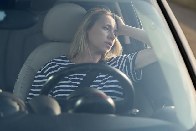 심한 교통 체증에 좌절하는 차의 운전석에 성가신 피곤한 여성은 피로 스트레스를 겪습니다