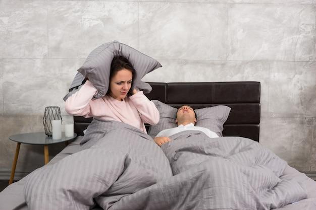 灰色のロフトスタイルで寝室のベッドでいびきをかく夫の音から枕で彼女の耳をブロックするイライラした妻