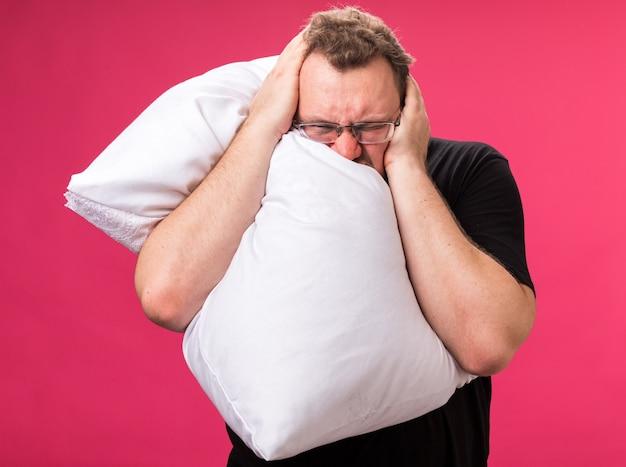 Infastidito con gli occhi chiusi maschio malato di mezza età abbracciato cuscino coperto le orecchie con le mani