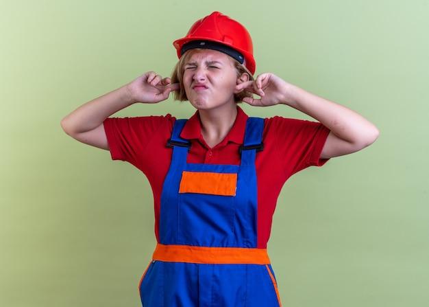 目を閉じてイライラするオリーブグリーンの壁に隔離された均一な閉じた耳の若いビルダーの女性