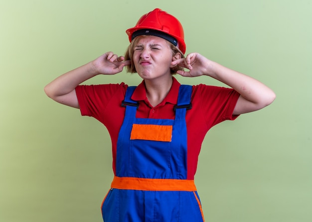 Annoyed with closed eyes young builder woman in uniform closed ears isolated on olive green wall
