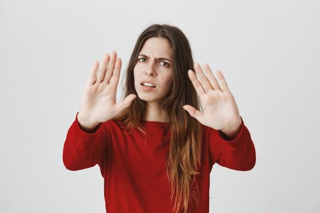 Раздражаемая женщина просит остановиться с вытянутыми руками, отказываясь или отвергая что-то