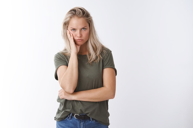 Annoyed woman cannot stand hearing lies leaning head on arm looking from under forehead irritated and intense with dismay and disrespect standing bothered and pressured over white background