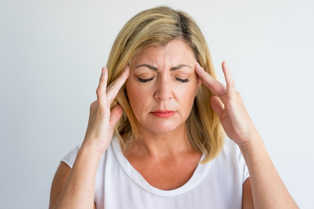 Annoyed woman feeling pain touching temples while trying to concentrate. Premium Photo