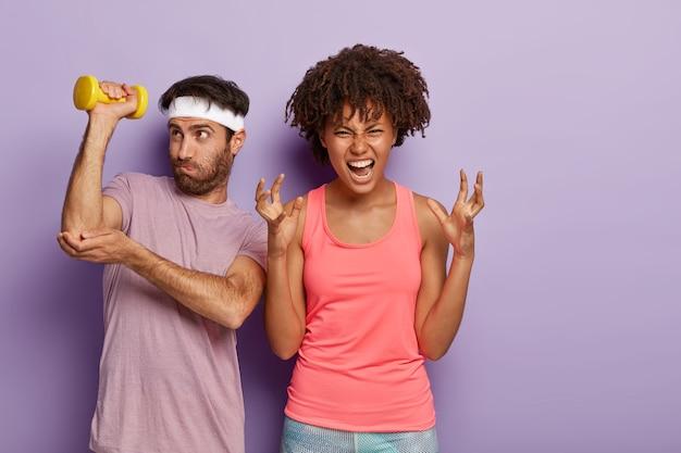 イライラした女性は怒ってジェスチャーをし、トレーニングを続けることができず、勤勉な男はスポーツウェアを着て筋肉を持っていることに取り組んでいます