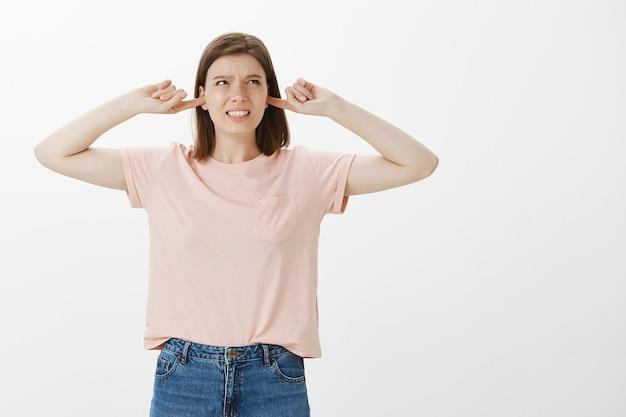 Раздраженная женщина морщится от громкого шума, закрывает уши и жалуется на раздражающий звук