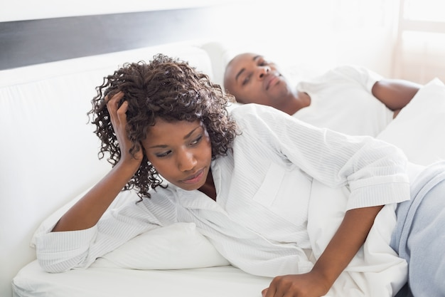 Annoyed woman lying in bed with boyfriend