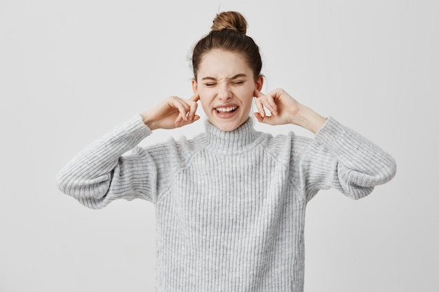 Annoyed woman plugging ears with fingers and screwing up her eyes in displeasure. brunette female covering ears complaining on loud music from outside. human feelings, reactions