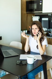 Annoyed woman sitting alone in kitchen at table at home holding smartphone gadget