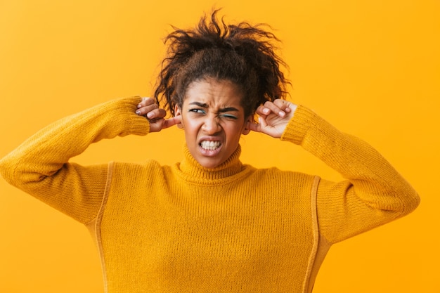 Annoyed young african woman wearing sweater standing isolated, cover ears