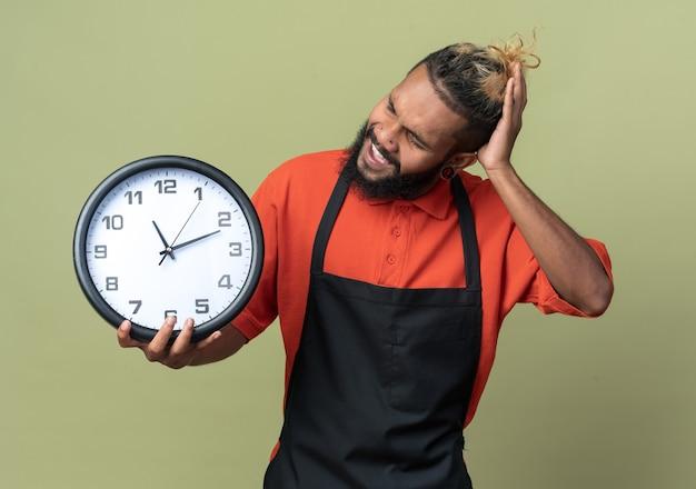 Раздраженный молодой афро-американский парикмахер в униформе держит и смотрит на часы, держа руку на голове, изолированную на оливково-зеленой стене