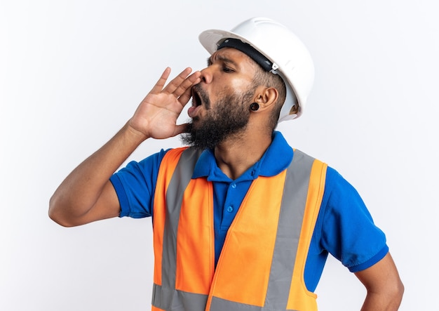 Annoyed young afro-american builder man in uniform with safety helmet keeping hand close to mouth calling someone looking at side isolated on white background with copy space