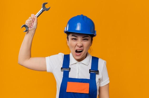 Раздраженная молодая азиатская девушка-строитель в синем защитном шлеме стоит с поднятой рукой, держащей ключ от мастерской