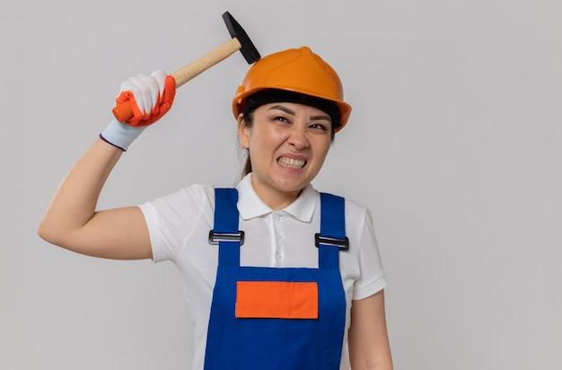 オレンジ色の安全ヘルメットとハンマーを保持している安全手袋でイライラする若いアジアのビルダーの女の子