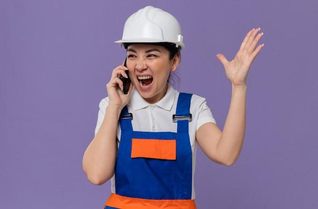 흰색 안전 헬멧을 쓴 화난 젊은 아시아 건축업자 소녀가 옆을 보고 있는 전화로 누군가에게 소리쳤다