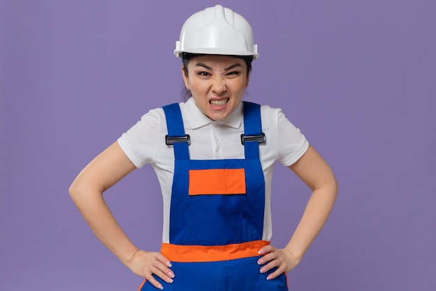 Annoyed young asian builder woman with white safety helmet putting hands on her waist and looking