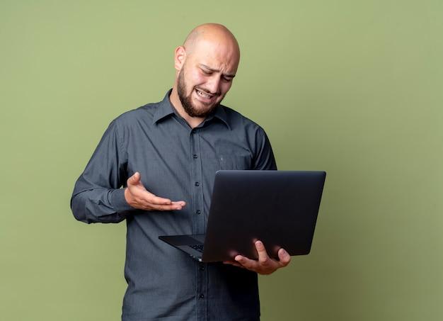 イライラした若いハゲのコールセンターの男は、ラップトップを持って見て、コピースペースとオリーブグリーンで隔離されたそれを手で指しています
