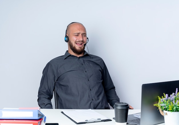 白で隔離のラップトップを見ている作業ツールと机に座っているヘッドセットを身に着けているイライラする若いハゲのコールセンターの男