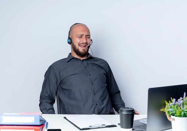 Infastidito giovane calvo call center uomo che indossa la cuffia avricolare seduto alla scrivania con strumenti di lavoro guardando il computer portatile isolato su bianco