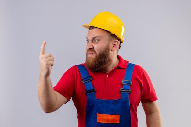 Infastidito giovane barbuto uomo costruttore in uniforme da costruzione e casco di sicurezza che guarda da parte con la faccia arrabbiata che punta il dito verso l'alto