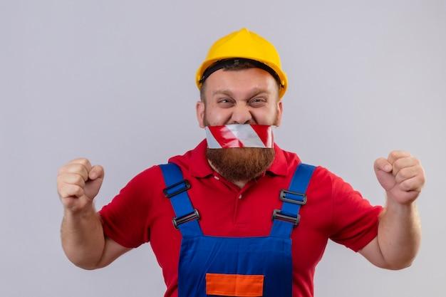 공격적인 표정으로 주먹을 떨리는 그의 입에 테이프로 건설 유니폼 및 안전 헬멧에 짜증이 젊은 수염 작성기 남자