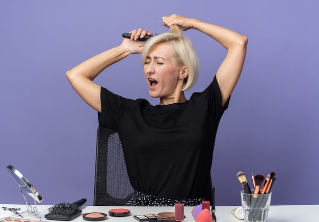 Раздраженная молодая красивая девушка сидит за столом с инструментами для макияжа, расчесывая волосы, изолированные на синей стене