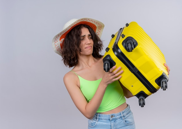 Раздраженная молодая красивая женщина-путешественница в шляпе и держит чемодан на изолированной белой стене с копией пространства