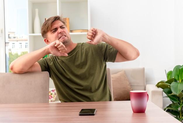 짜증이 젊은 금발의 잘 생긴 남자는 거실 내부 측면을보고 주먹을 유지 컵과 전화 테이블에 앉아 무료 사진