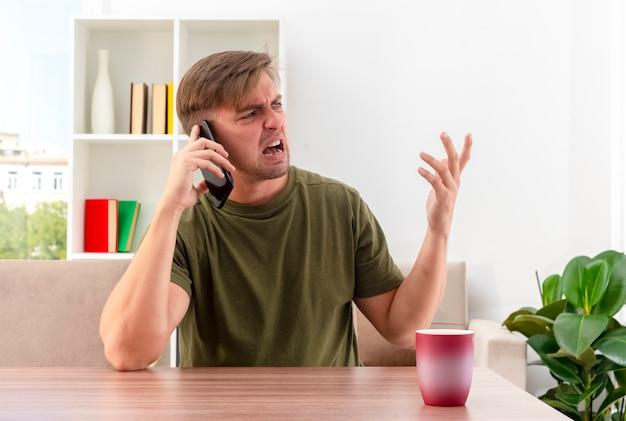 イライラする若いブロンドのハンサムな男は、横を見て上げられた手で電話で誰かに叫んでカップとテーブルに座っています