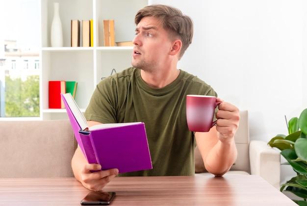 Раздраженный молодой блондин красавец сидит за столом с телефоном, держит книгу и чашку, глядя в сторону внутри гостиной