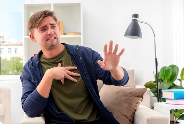 イライラする若い金髪のハンサムな男が肘掛け椅子に座って手を上げて横を見て