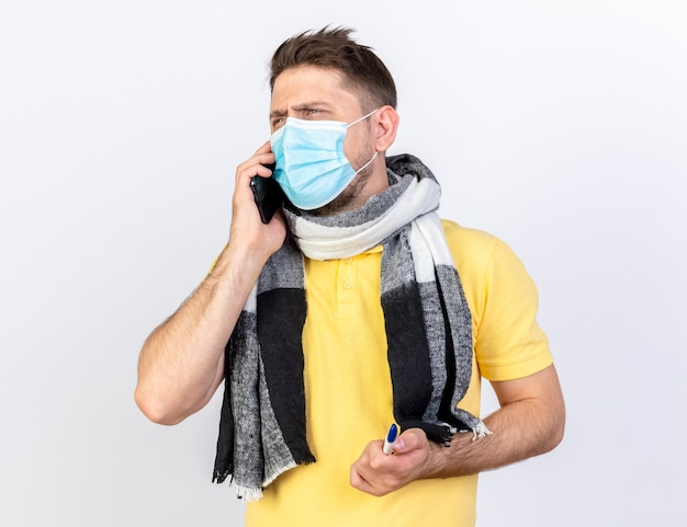 Annoyed young blonde ill man wearing medical mask and scarf talks on phone holds thermometer isolated on white wall