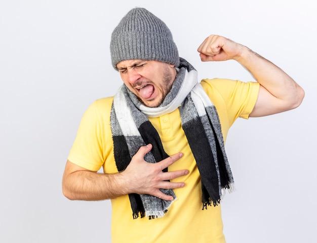 Раздраженный молодой блондин больной в зимней шапке и шарфе напрягает бицепсы, кладет руку на грудь, изолированную на белой стене