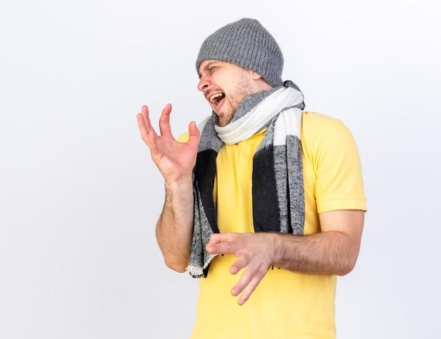 겨울 모자와 스카프를 착용하는 짜증이 젊은 금발의 아픈 슬라브 남자