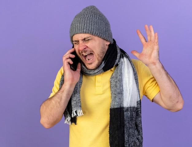 冬の帽子とスカーフを身に着けているイライラする若い金髪の病気のスラブ人