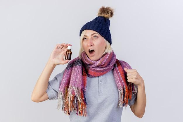 冬の帽子とスカーフを身に着けているイライラする若い金髪の病気のスラブの女性は、ガラス瓶に薬を保持し、コピースペースで白い壁に隔離された拳を見上げ続けます