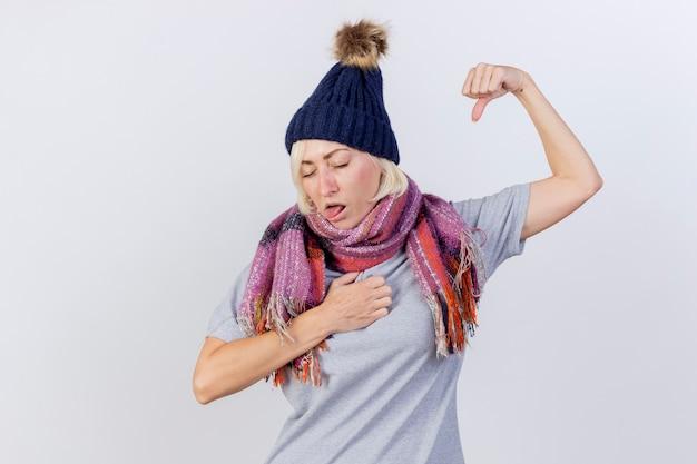 冬の帽子とスカーフを身に着けているイライラする若い金髪の病気のスラブ女性は、胸に拳を置き、コピースペースで白い壁に分離された上腕二頭筋を緊張させる