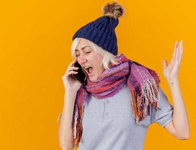 冬の帽子とスカーフスタンドを身に着けているイライラする若い金髪の病気のスラブ女性